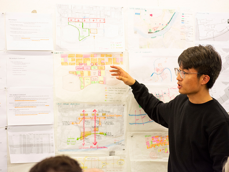 MSUD student presents drawings for his ULI Hines Design Competition project entry in the Hinman Research Building.