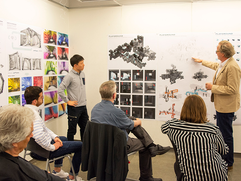 Students and faculty review work on a pin-up wall at a Final Review in the Hinman Research Building.