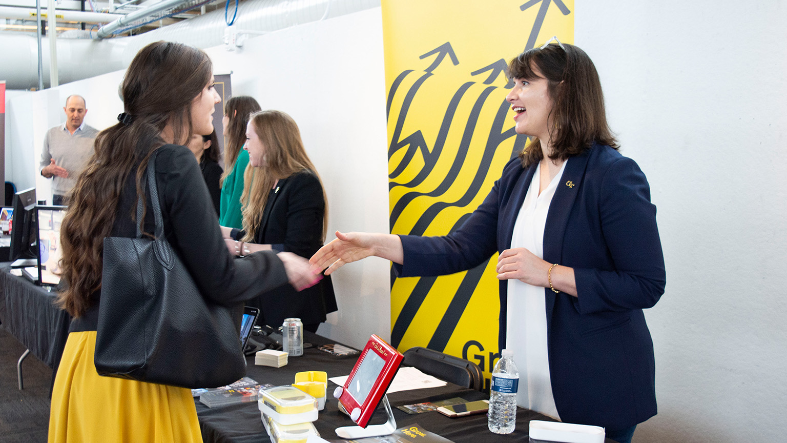 A student and an architecture professional shake hands at the 2020 Career Fair in the Architecture West atrium