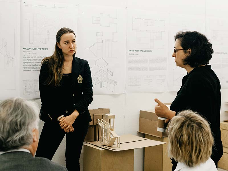 Guest juror gives student feedback during a final review presentation in the Architecture West third floor atrium.
