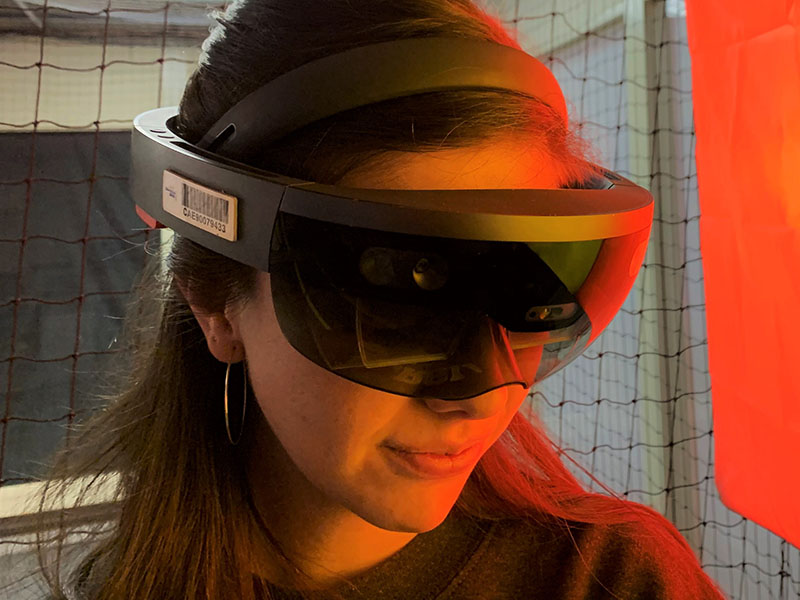 Graduate Assistant for Keith Kaseman's Spatial Futures Lab, Dani Marquez, wearing a Microsoft Hololens for the droneport project in the Digital Fabrication Lab.