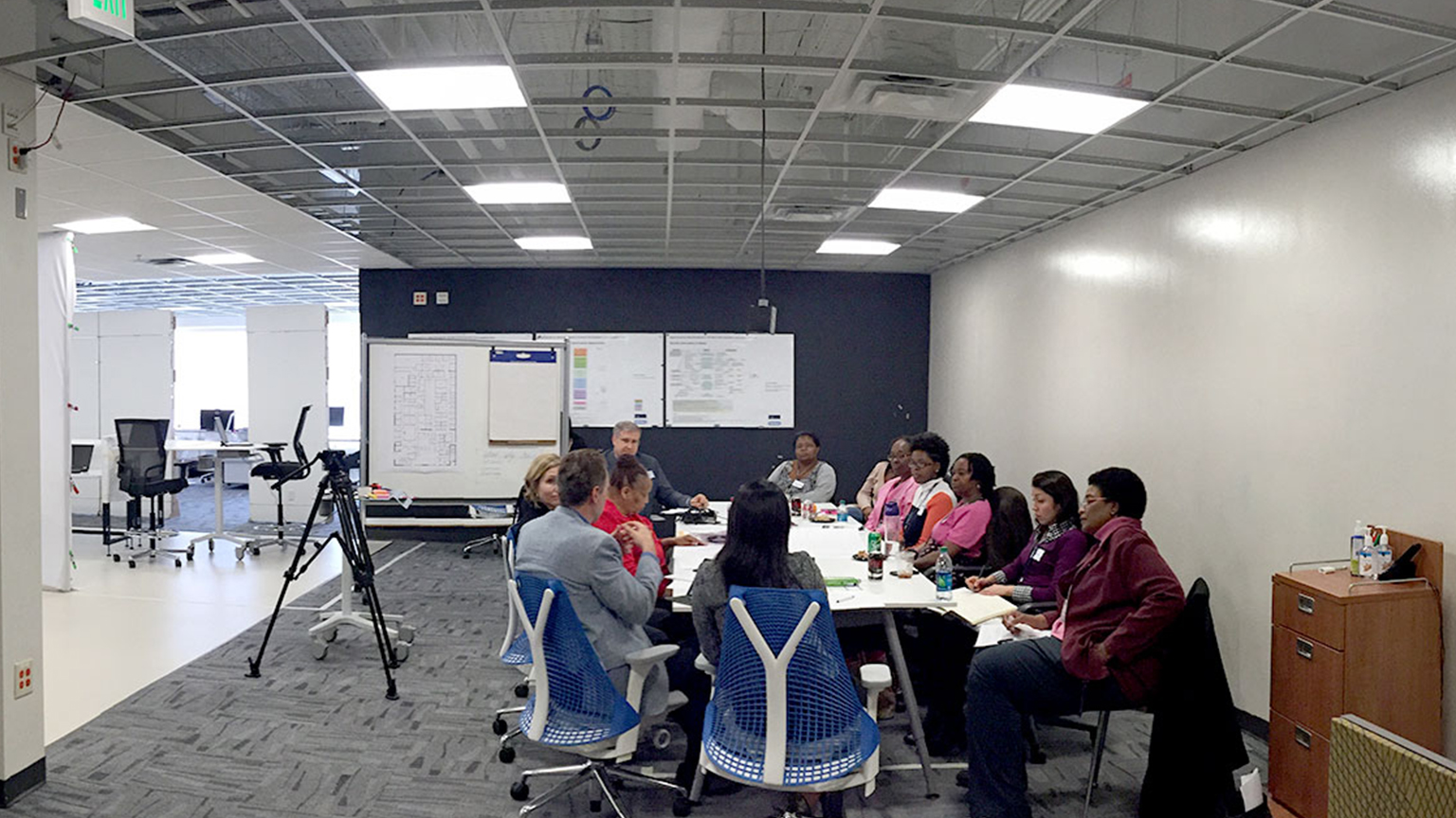A group of participants meeting around a conference table in the SimTigrate Design Lab