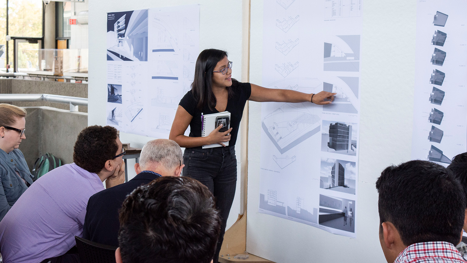 Student presenting a project in the Architecture West third floor atrium for a Junior Studio review.