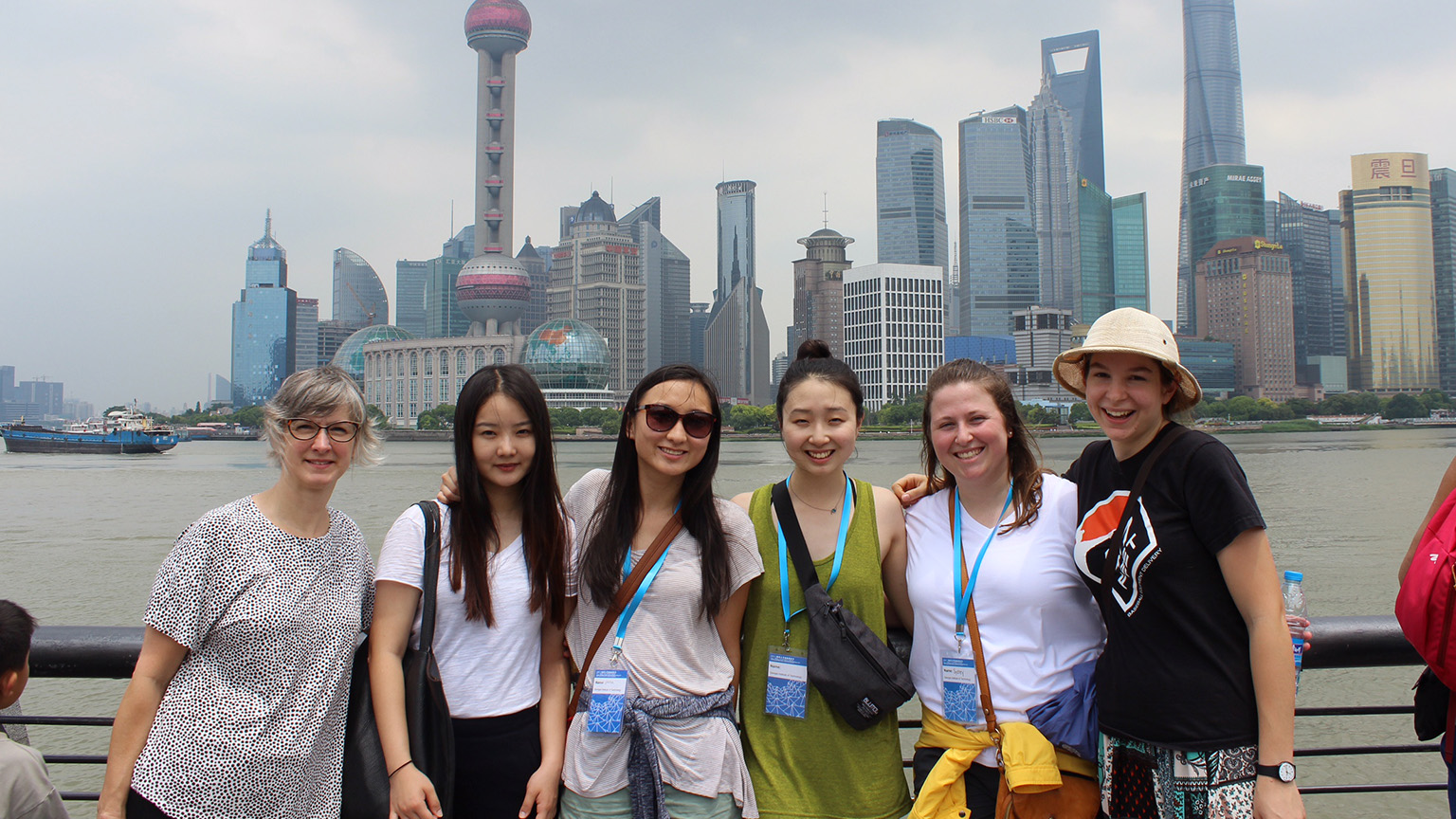 Michelle Rinehart and first-year students in front of the Shanghai skyline.
