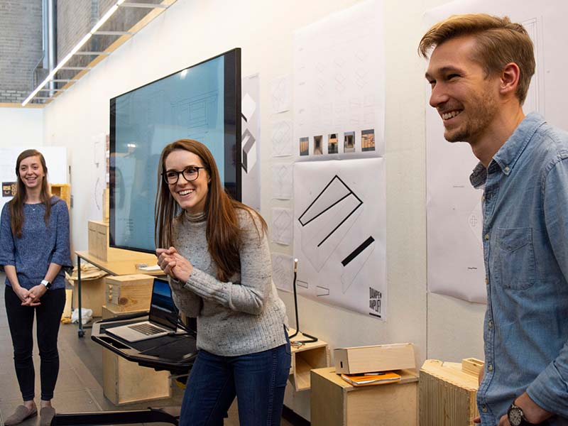 Three students present a project on a monitor in the Hinman Research Building