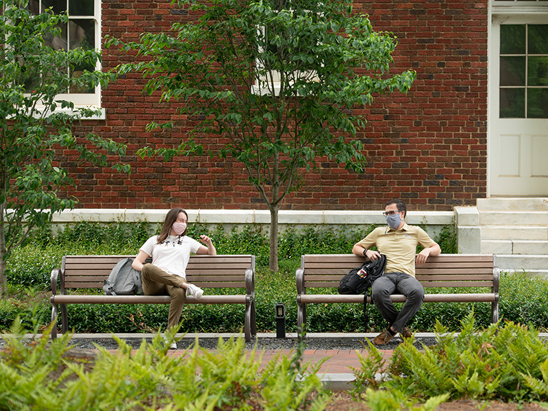 Students sitting on benches at Georgia Tech wearing masks and talking to one another.