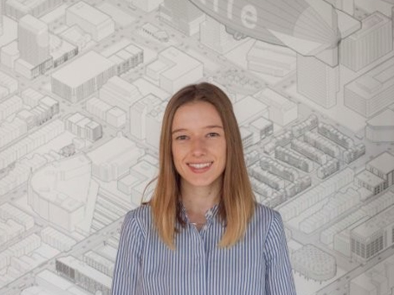 Katie Reilly's headshot with a large architecture drawing in the background.