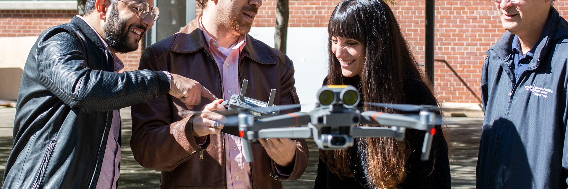 Ph.D. researchers and assistant professor, Tarek Rakha, flying a drone in the Hinman Courtyard.