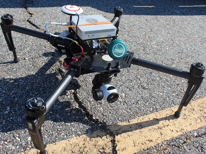Drone equipped with advanced sensors sitting over cracked pavement.