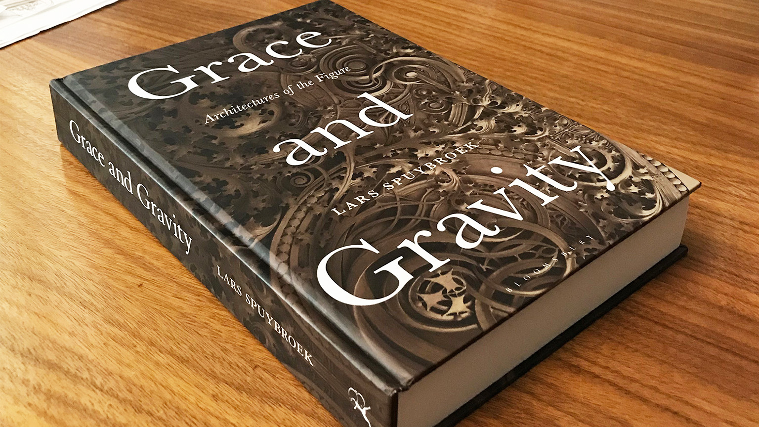 A copy of the book Grace and Gravity by Professor Lars Spuybroek sitting on a desk.